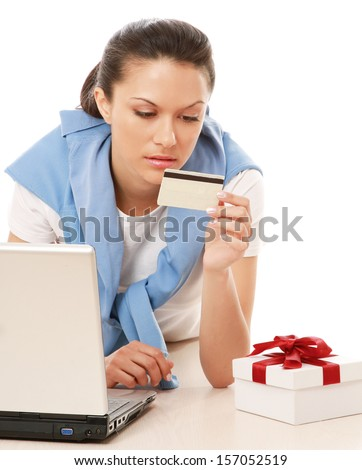 A young woman lying on the floor with a laptop, holding a credit card and a gift box - stock photo