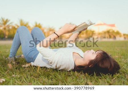A young woman lying on the grass and reading a book - stock photo