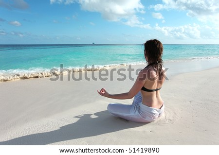 A young woman maditating at a maldivian beach
