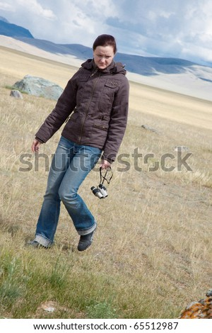 A young woman makes a walk in the desert in windy weather