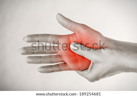 A young woman massaging her painful hand on a gray background - stock photo