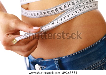 A young woman measuring her waist isolated on white background - stock photo