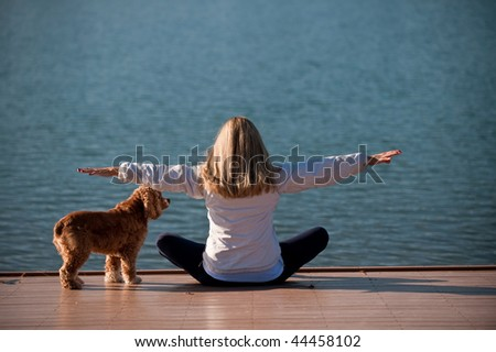 A young woman meditate by a lake - stock photo