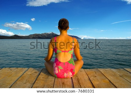 A young woman meditating and relaxing during evening hours in an amazing scenery - stock photo