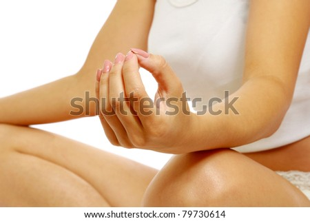 A young woman meditating, closeup, focus on her hands, isolated on white