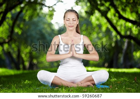 A young woman meditating in park - stock photo