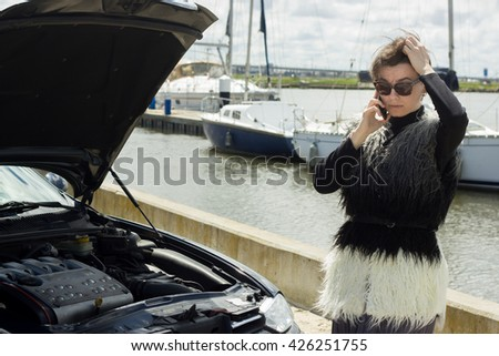 A young woman near the broken car, talking on the phone. Worried expression. The car breakdown concept. With shallow depth of field. - stock photo