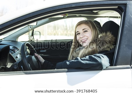 A Young woman new car and smiling at camera