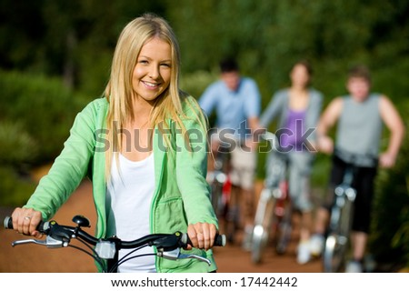 A young woman on a bike with group of friends in background