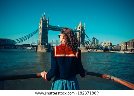 A young woman on a boat is looking at Tower bridge and the London skyline - stock photo
