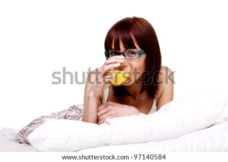 A young woman on her bed relaxing in the morning. Breakfast in bed.