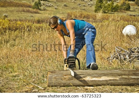 A young woman operating a chainsaw - stock photo