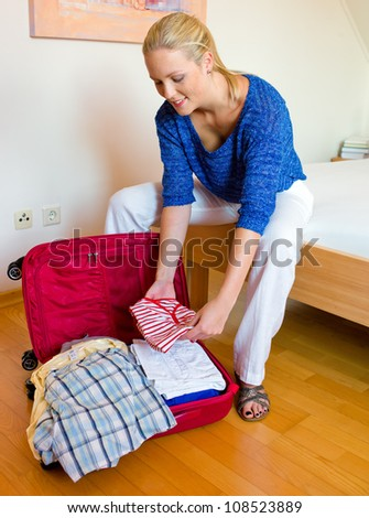 a young woman packing her suitcase for the trip to the holiday.