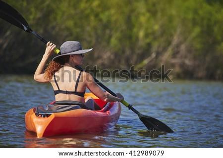 a young woman paddling a kayak - stock photo