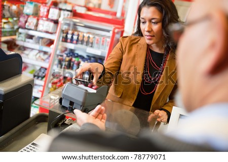 A young woman paying for grocery purchase with a mobile phone - stock photo