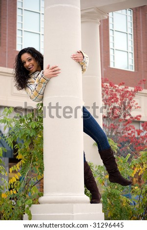 A young woman playing around on a large pillar outside. - stock photo