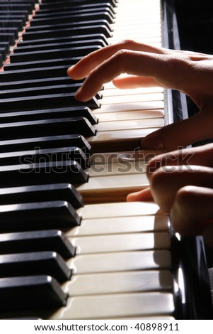 A  young woman playing piano closeup - stock photo