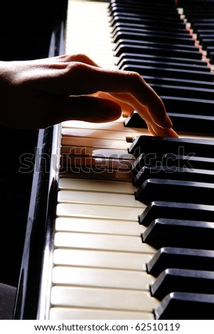 A  young woman playing piano closeup - stock photo