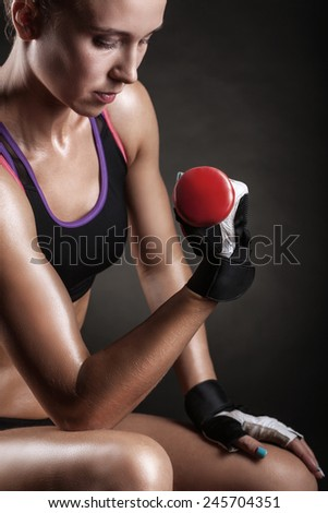A young woman playing sports with weights on a dark background - stock photo