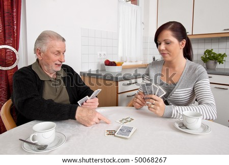 A young woman plays with seniors in their free time with playing cards - stock photo