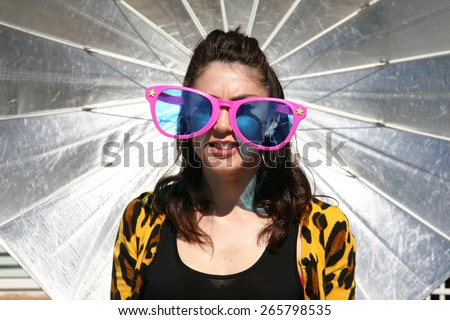 A young woman poses as a Fashion Model against a large Silver Photo Studio Parabolic umbrella.  - stock photo