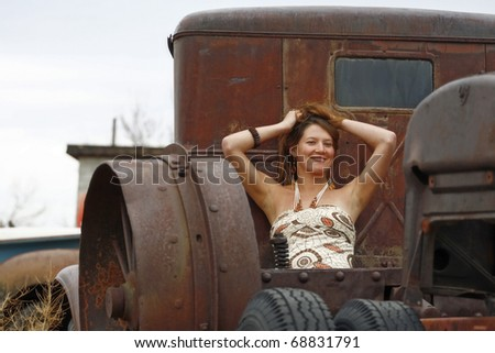 A Young Woman Posing in the Bed of an Antique Truck - stock photo