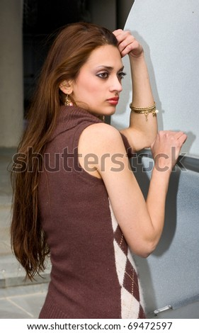 a young woman posing next to a sculpture. - stock photo