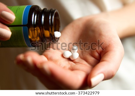 A young woman pours the pills out of the bottle - stock photo