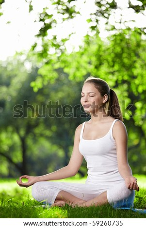 A young woman practices yoga in the park - stock photo