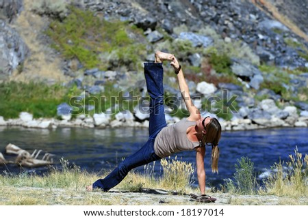 A young woman practices Yoga on the river.