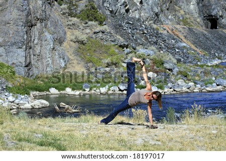 A young woman practices Yoga on the river. - stock photo