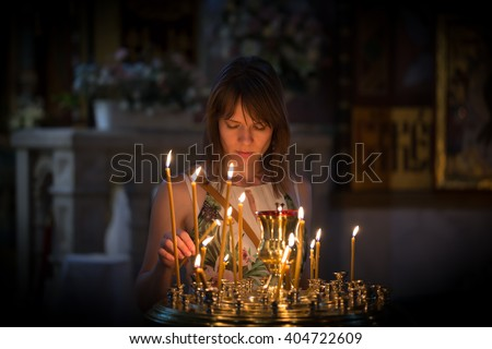 A young woman praying in a church - stock photo