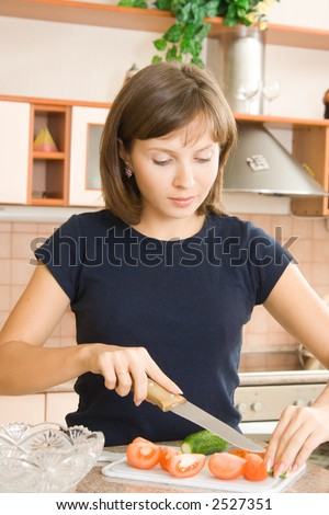A young woman preparing salad in the kitchen - stock photo