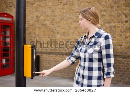 a young woman pressing the button to cross the road - stock photo