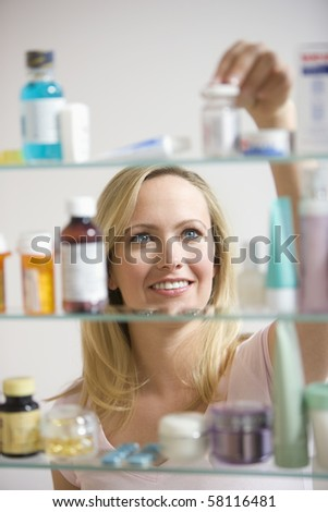 A young woman reaches for a container in her medicine cabinet.  Vertical shot. - stock photo