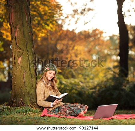 A young woman reading a book in the city park - stock photo