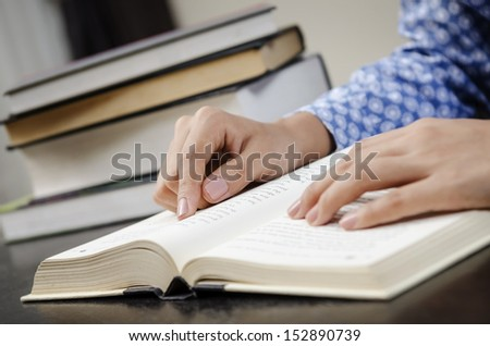 A young woman reading a book in the library - stock photo