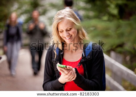 A young woman reading a friendly text while outdoors - stock photo