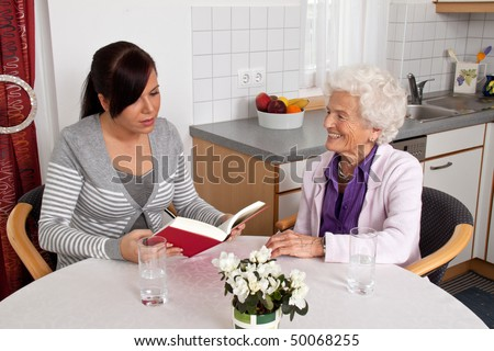 A young woman reads seniors from a book. - stock photo