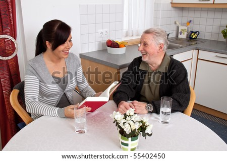 A young woman reads to seniors from a book. - stock photo