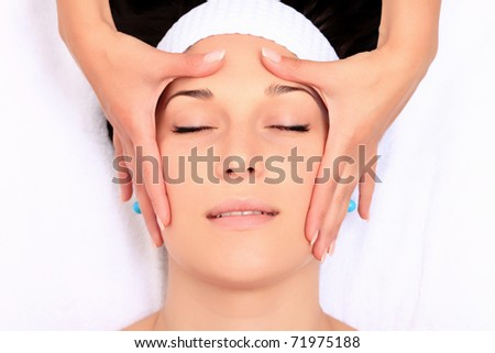 A young woman relaxing at a health spa while having a facial treatment. - stock photo