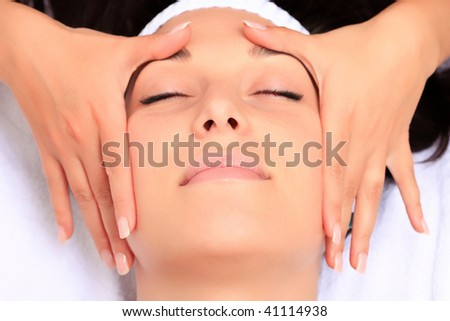 A young woman relaxing at a health spa while having a facial treatment and hands massaging. - stock photo