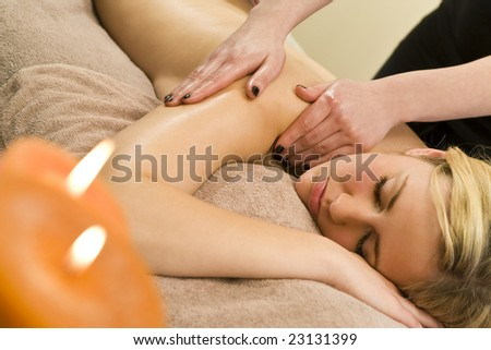A young woman relaxing at a health spa while having a massage - stock photo