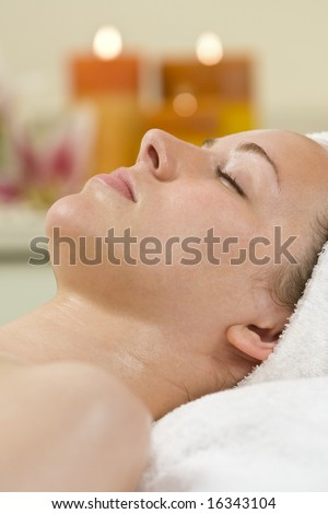 A young woman relaxing at a health spa with candles creating a warm and calming atmosphere