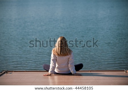 A young woman relaxing by a lake - stock photo