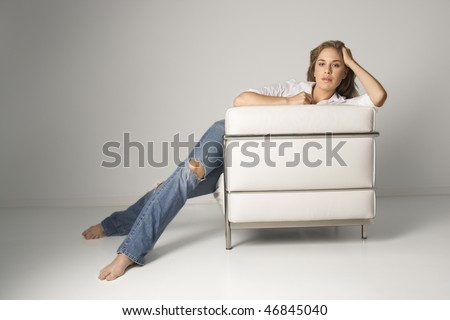A young woman relaxing in a white armchair and looking at the camera. Horizontal shot. - stock photo