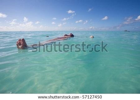 A young woman relaxing on the water surface - stock photo