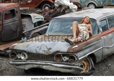 A Young Woman Resting on an Old Car - stock photo