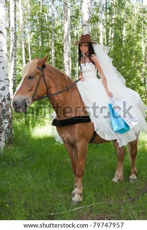 a young woman riding a horse in a birch