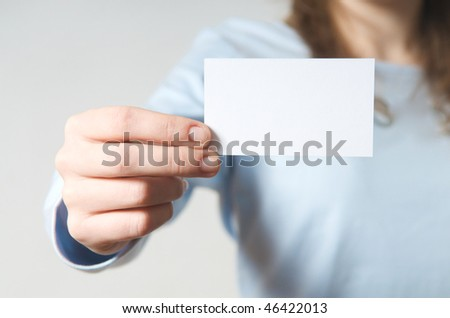 A young woman's hand holding a blank business card